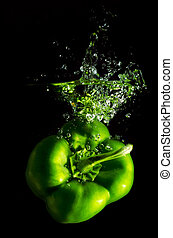 green pepper falls in the water before black background