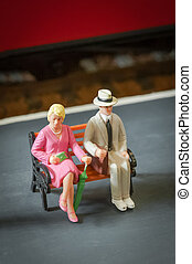 miniature people seated on a bench on a railway platform