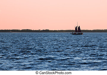 Old sail ship silhouette in sunset in sea