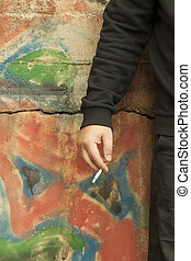 Man's hand with a cigarette on the graffiti wall