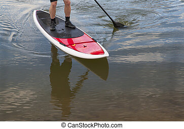 paddling stand up paddleboard on a lake - feet and legs of...