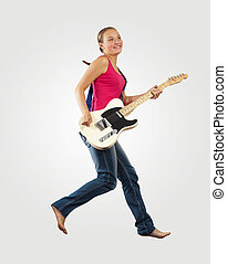 young woman playing on electro guitar and jumping
