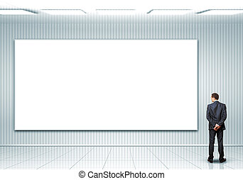 Business person standing near a blank billboard - Business...
