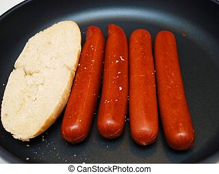 Frying sausages in a non-stick frying pan, with white bread