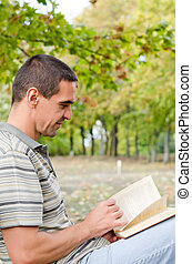 Man sitting outdoors reading a novel - Attractive tanned man...