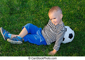 Youngster lying against his soccer ball on green grass in...
