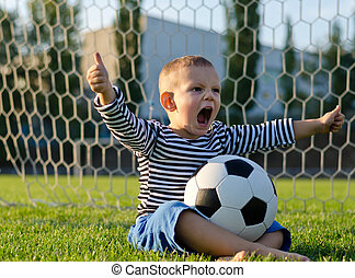 Boy with football shouting with glee - Small boy with a...