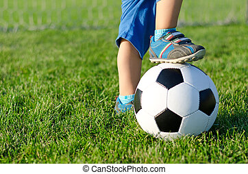 Boy with his foot on a soccer ball - Little boy in shorts...