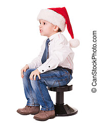 Angry kid  in santa hat on chair
