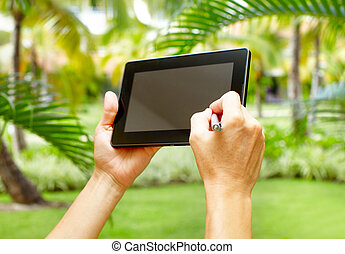 Hands with tablet computer in tropical garden.  Vacation.