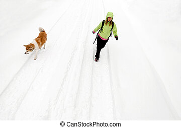 Woman hiking with dog on winter road and snow