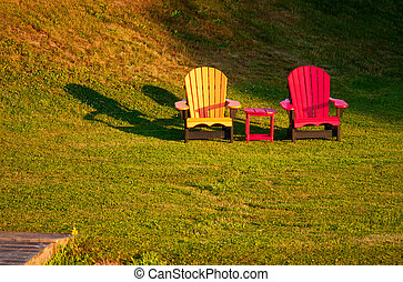 Two brightly painted chairs on a lawn