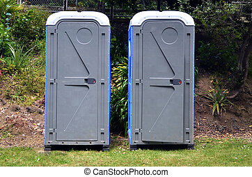 Two portable bathrooms in the field of a camp ground
