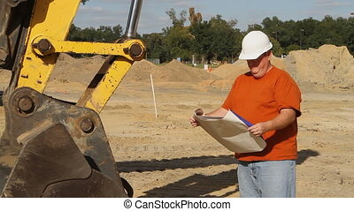 Construction Foreman Texting - Construction foreman stands...
