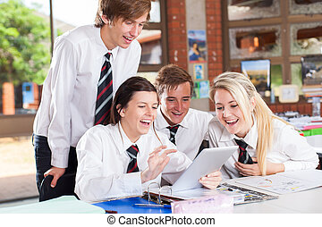 high school students using tablet computer - group of happy...