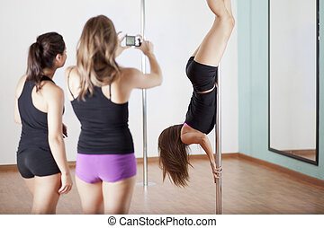 Pole fitness demonstration - Pole fitness students looking...