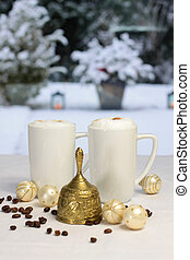 Golden Christmas bell and coffee cups, Christmas balls and coffee beans in front of winter terrace