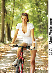 Peaceful bike ride - Young woman on a bicycle in the forest