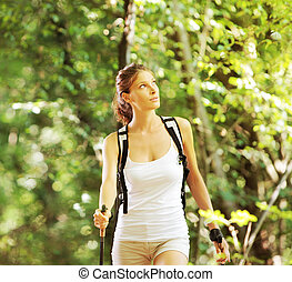 Nordic walking - Woman walking cross country in forest