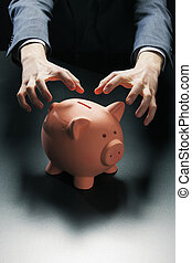 Robbing the Piggy Bank - Hands reaching for a piggy bank