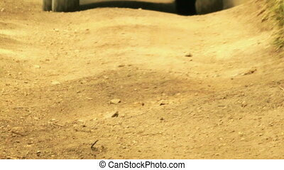 Close up view of ATV wheels in terrain. - Close up view of...