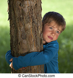 Little boy embracing a tree in a park