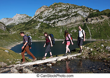Hiking in the mountains - Young people cross a brook in the...