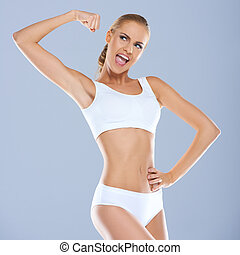 Portrait of young woman in white sportsbra smiling