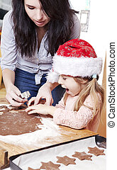 chistmas baking - mum and her daughter cutting gingerbread...