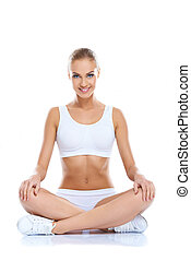 Happy young woman sitting with legs crossed on isolated