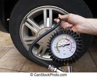 Checking Tire Pressure - Close-up of manometer and man hands...