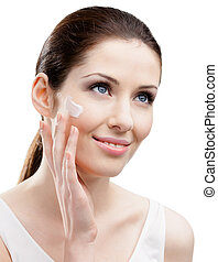 Woman applying cream on her face, isolated on white. The...