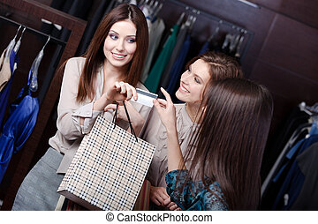 Women take away purchases - Pretty women pay with credit...