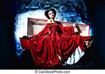waking up - Bloodthirsty female vampire rises from the...