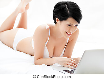 Woman in underwear is working on the computer while lying on...