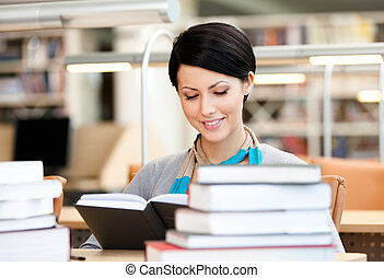 Attractive girl reads at the library - Woman surrounded with...
