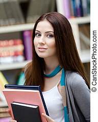 Female student with books at the library. Research. Study