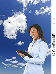 Happy woman with tablet computer and clouds - Smiling black...