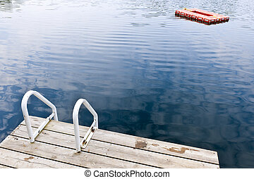 Dock on calm summer lake - Dock and ladder on calm summer...