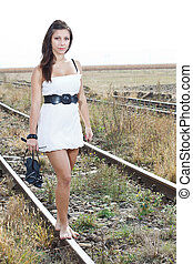 Young woman barefeet on rail