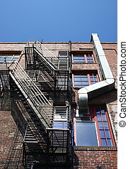 Black Fire Escape and Metal Ductwork - An old brick building...