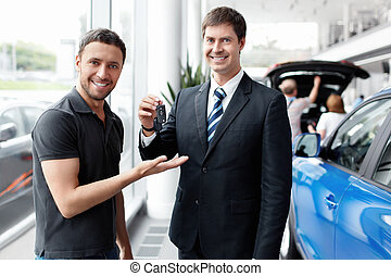 Happy shopper - Seller gives the buyer of the car keys