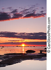 Beautiful sunset at sea, large rocks in foreground