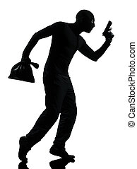 thief criminal holding gun in silhouette studio isolated on...