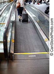 Moving walkway in the airport. Passenger with a bag.