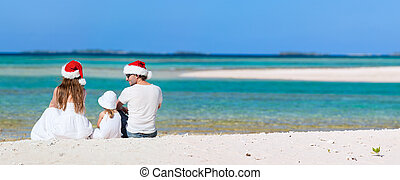 Christmas vacation - Young parents in Santa hats and their...
