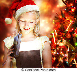 Girl Opening a Gift Box - Happy Blonde Girl with Santa Hat...