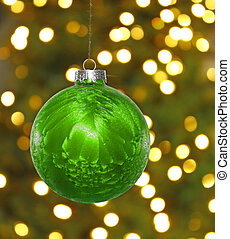 A big green hanging Christmas ball decoration in front of a...
