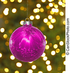 A big pink hanging Christmas ball decoration in front of a...