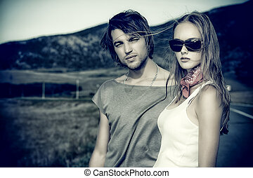 couple on road - Couple of modern young people posing on a...
